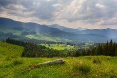 Bergen, het dorp en de stormachtige hemel stock foto
