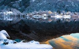 Bergen, Hordaland, Noorwegen De sneeuwbergen en de kleurrijke glanzende wolken dachten in Haukeland-meer in suburbia van Bergen i royalty-vrije stock afbeeldingen