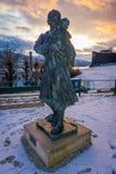 BERGEN NORGE - APRIL 03, 2018: Den utomhus- sikten av statyn av kvinnan och behandla som ett barn i den Bergen hamnen, under en s Arkivfoto