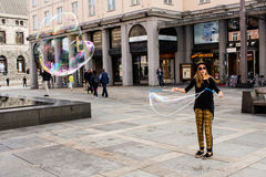 BERGEN, NORWAY - CIRCA 2016: A female street performer creates large bubbles in the main city square of Bergen. BERGEN, NORWAY - CIRCA 2016: A female street Royalty Free Stock Photos
