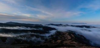 Bergen och dimmadrömmen dem emellan på horizonten Royaltyfria Bilder