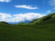 Bergen op horizon met ronde vormen, betrokken blauwe hemel, weiden in voorgrond, royalty-vrije stock foto's