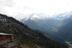 Bergen in sneeuw met wolken op achtergrond worden behandeld die Royalty-vrije Stock Afbeeldingen