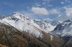 Bergen in sneeuw met wolken op achtergrond worden behandeld die Royalty-vrije Stock Foto