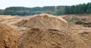 Bergen van zand in het bos bij de bouwwerf van nieuw stock fotografie