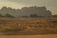 Bergen in Wadi Rum-woestijn met woestijnweg en kleine auto royalty-vrije stock afbeelding