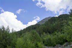 Berget med gröna träd, blå himmel, vit fördunklar i utlöparen av Elbrus, norr Kaukasus, Ryssland Arkivbild