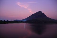 Berget och reflexionen på sjön ytbehandlar i skymningen Royaltyfri Foto