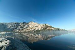 Berget och sörjer träd som reflekterar på den alpina sjön Royaltyfri Bild