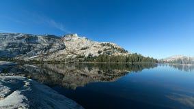 Berget och sörjer träd som reflekterar på den alpina sjön Arkivfoto