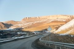 Berget som är slingrande till och med byn i de Kaukasus bergen med epos, vaggar på baksidan av det polan trafik för tecken för rö royaltyfria foton