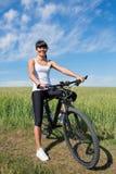 Berget som cyklar den lyckliga sportive flickan, kopplar av i solig bygd för ängar Royaltyfri Bild