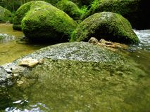 Bergflod med stenblock och stenar Arkivfoto