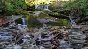 Bergflod med välsignelse balanserade Zen Stone Structures på banker som flödar i himalayasna Forest Creek med rent lager videofilmer