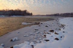 Bergfloden i aftonen Stenar och snöbank Royaltyfri Bild
