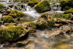 Bergfloden med kaskaden och enormt vaggar Arkivfoto