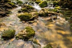 Bergfloden med kaskaden och enormt vaggar Royaltyfria Foton