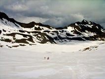 Bergfolk som går på glaciären Arkivfoto