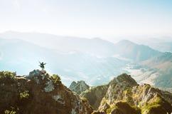 Bergfotvandraren med den mycket lilla statyetten f?r ryggs?cken st?r p? bergmaximum med h?rlig panorama fotografering för bildbyråer