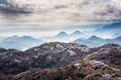Berghöstlandskap med bergmaxima på havskust med dramatisk himmel i mulen dag med mist i det Europa landet Monten arkivfoto