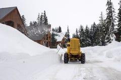 Berghütte-Straße mit gelber Schneeräumungs-Maschine Stockfotos