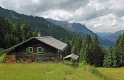 Berghütten in den österreichischen Alpen, gegen drastische Wolken Lizenzfreie Stockbilder
