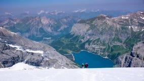 Berghandbok med två klienter som stiger ned en brant vit glaciär med en fantastisk blå bergsjö långt under fotografering för bildbyråer