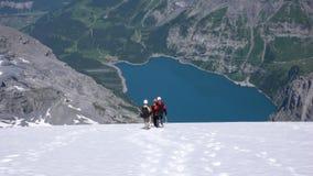 Berghandbok med två klienter som stiger ned en brant vit glaciär med en fantastisk blå bergsjö långt under royaltyfri bild