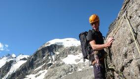 Berghandbok på en brant och utsatt stenig kant på hans väg till en hög alpin toppmöte med en klient royaltyfri bild