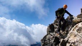 Berghandbok på en brant och utsatt stenig kant på hans väg till en hög alpin toppmöte med en klient fotografering för bildbyråer