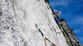 Berghandboken som klättrar en brant tjock skivagrad av ett hårt, vaggar klättringrutten i fjällängarna av Schweiz arkivfoto