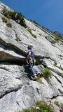 Berghandboken som klättrar en brant tjock skivagrad av ett hårt, vaggar klättringrutten i fjällängarna av Schweiz arkivbilder