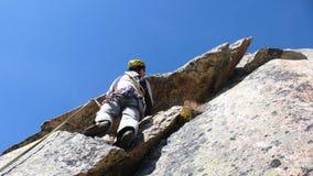Berghandboken vaggar klättraren på en brant granitrutt i fjällängarna av Schweiz på en härlig dag royaltyfria bilder