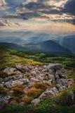 Bergheuvel met stormachtige hemel en zonnestraal bij zonsondergang royalty-vrije stock fotografie