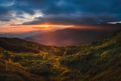Bergheuvel met stormachtige hemel en zonnestraal bij zonsondergang stock fotografie