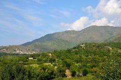 Berghimmel och hem i by av flugsmälladalen Khyber Pakhtoonkhwa Pakistan fotografering för bildbyråer