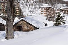 Berghuizen met sneeuw worden behandeld die Stock Foto's
