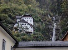 Berghus med vattenfallet arkivbild