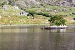 Berghus vid sjön med ön Fotografering för Bildbyråer