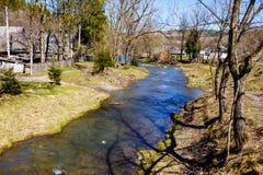 Bergig flod som flödar till och med liten by tidig fjäder arkivbild