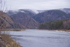 Bergig kust av floden i dimman arkivfoto