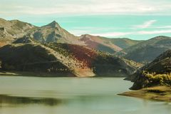 Bergigt naturligt landskap med sjön i förgrund, land av olika färger royaltyfri bild
