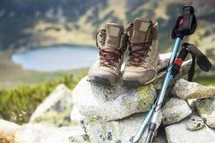 Bergkängor och trekking pinnar på bergmaximum Arkivfoton