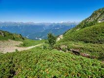 Bergketen en vallei met woonhuizen, mening van een hoogte De stroom van de berg stock afbeeldingen