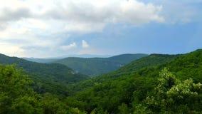 Bergketen met zichtbare silhouetten van pieken die door de nevel tegen de blauwe hemel en de witte wolken verschijnen stock video
