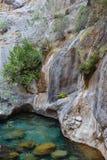 Bergklippor som stiger ned till den kristallklara floden Royaltyfri Fotografi
