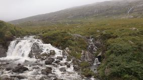 Bergkreek die schot met kleine waterval vestigen stock footage