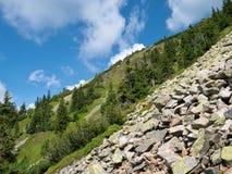 Bergkullen med stenar och blå himmel med något fördunklar Arkivfoton
