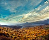 Berglandschaft, Herbstwald auf einem Abhang, unter dem Himmel Stockbilder