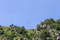 Berglandschaft mit einem hochfliegenden Adler über den Felsen Lizenzfreie Stockbilder